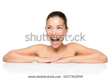 Skin care beauty woman looking up at copy space for product. Excited screaming happy smiling mixed race Asian Caucasian female beauty model girl isolated on white background leaning above towel.