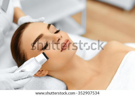 Skin Care. Close-up Of Beautiful Woman Receiving Ultrasound Cavitation Facial Peeling. Ultrasonic Skin Cleansing Procedure. Beauty Treatment. Cosmetology. Beauty Spa Salon. - stock photo