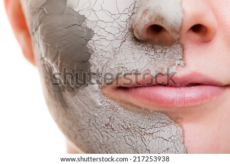 Skin care. Closeup of female face. Young woman applying clay mask. Girl taking care of her dry compexion. Isolated. Spa and beauty treatment. - stock photo
