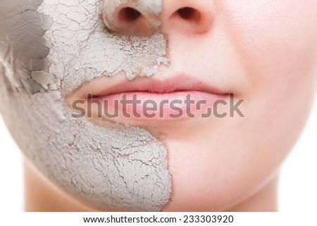 Skin care. Closeup of female face. Young woman applying clay mask. Girl taking care of her dry complexion. Isolated. Spa and beauty treatment. - stock photo