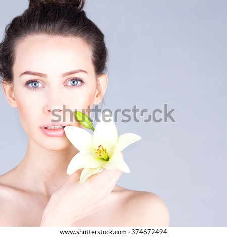 Skin care. Face of woman with lily. SPA and beauty.