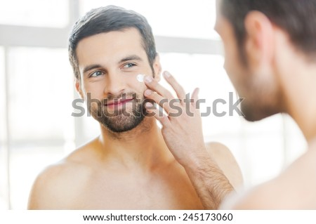 Skin care. Handsome young shirtless man applying cream at his face and looking at himself with smile while standing in front of the mirror  - stock photo