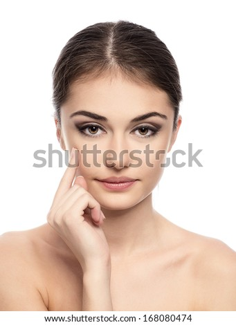 Skin care. Lovely female brunette applying cream on her face. Close-up of beauty Caucasian woman model isolated over white background.