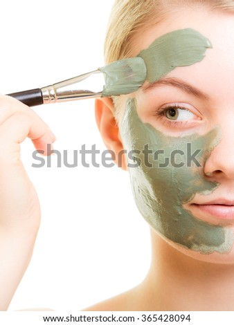 Skin care. Woman applying with brush clay mud mask on face isolated. Girl taking care of dry complexion. Beauty treatment.