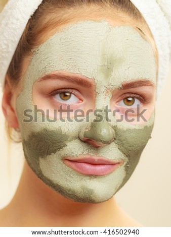 Skin care. Woman face with green clay mud mask close up. Girl taking care of oily complexion. Beauty treatment.