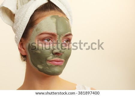 Skin care. Woman face with green clay mud mask. Girl taking care of oily complexion. Beauty treatment. - stock photo