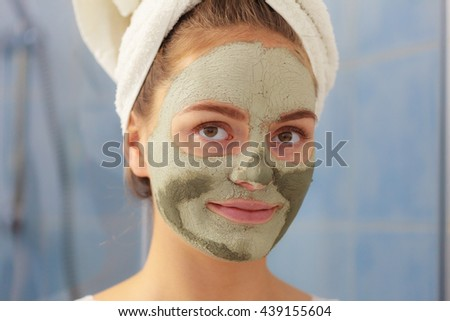 Skin care. Woman in bathroom with green clay mud mask on face. Girl taking care of oily complexion. Beauty treatment.