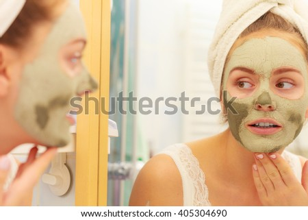 Skin care. Woman in bathroom with green clay mud mask on face looking at mirror. Girl taking care of oily complexion. Beauty treatment. - stock photo