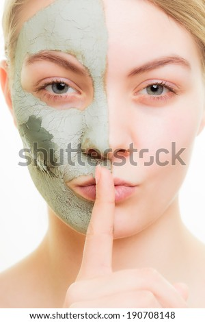 Skin care. Woman in clay mud mask on face with finger on lips isolated on white. Girl taking care of dry complexion. Secret of beauty. - stock photo