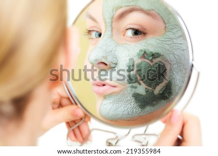 Skin care. Woman in clay mud mask on face with heart on cheek looking in the mirror isolated on white. Girl taking care of dry complexion. Beauty treatment. - stock photo