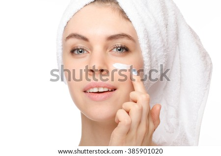 Skin care woman putting face cream touching under eyes. Facial beauty closeup of beautiful female model on white background. - stock photo