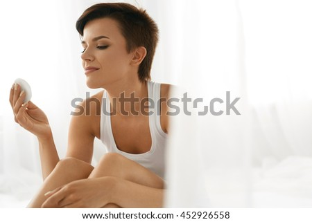 Skin Care. Woman Removing Face Makeup With Cotton Pad. Close Up Portrait Of Beautiful Healthy Girl With Nude Makeup Touching Perfect Soft Skin, Cleaning Fresh Face With Facial Tonic. Beauty Concept