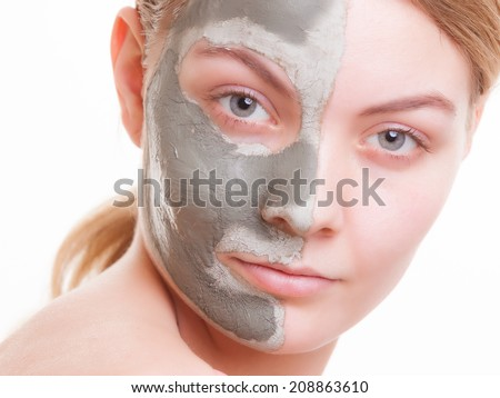 Skin care. Young woman applying clay mask on her face. Girl taking care of her dry compexion. Isolated. Spa and beauty treatment.