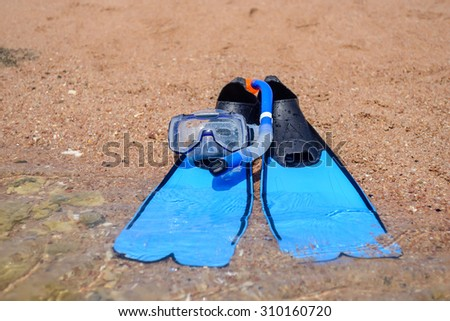Skin diving gear lying ready on the beach with a snorkel, goggles and pair of flippers conceptual of an active summer vacation - stock photo