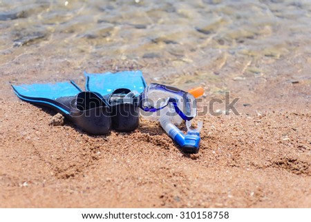Skin diving gear with a pair of flippers, goggles and snorkel lying on the sand at the edge of the ocean on a tropical beach - stock photo