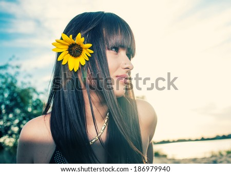 Skincare and beauty face. Sensual girl profile view with sunflower in her long healthy hair outdoors. - stock photo