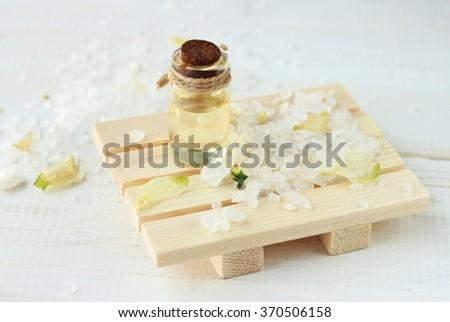 Skincare aroma oil in bottle, herbal sea salt scrub. - stock photo
