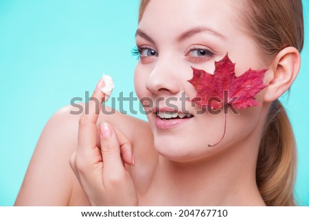 Skincare habits. Face of young woman with leaf as symbol of red capillary skin on turquoise. Girl taking care of her dry complexion applying moisturizing cream. Beauty treatment. - stock photo