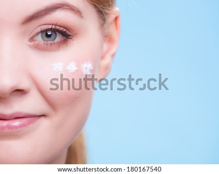 Skincare habits. Part of face of young woman as symbol of red capillary skin on blue. Girl taking care of her dry complexion applying moisturizing cream. Beauty treatment. - stock photo