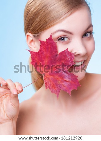Skincare habits. Portrait of young woman with leaf as symbol of red capillary skin on blue. Face of girl taking care of her dry complexion. Studio shot.