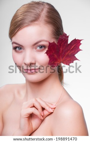 Skincare habits. Portrait of young woman with leaf as symbol of red capillary skin on gray. Face of girl taking care of her dry complexion. Studio shot.