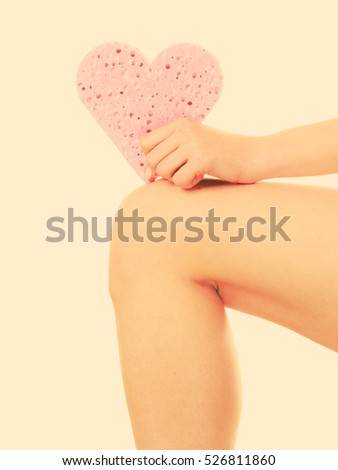 Skincare hygiene health and body treatment. woman perfect skin holding pink heart shaped bath sponge in hand.