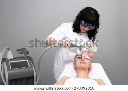 Skincare laser pigment color change at day spa being preformed on face of woman by technician. - stock photo