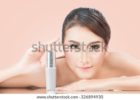 skincare products, Portrait of Beautiful Young Woman looking at Camera. Beautiful Asian female model on pink background with clipping path. - stock photo
