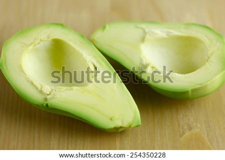 skinned avocado halves on wooden board - stock photo