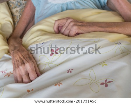 Skinny arms and hands of a very old woman lying in a bed