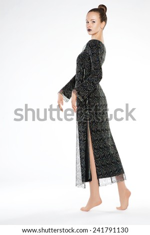skinny beautiful girl in the studio on a white background in a long green  dress - stock photo