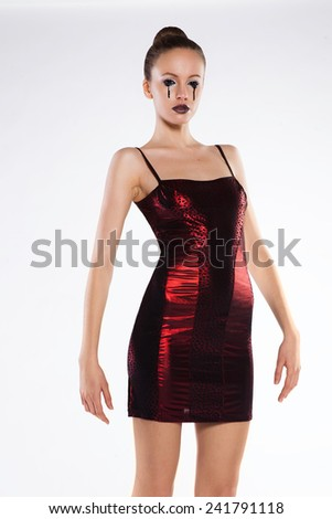 skinny beautiful girl in the studio on a white background in a short red dress - stock photo