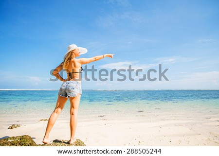 Skinny caucasian tanned woman stays on the rock against blue sky and pure ocean water, pointing with her hand. Travel, vacation, holidays, paradise concept, copyspace - stock photo
