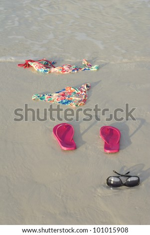 Skinny dipping concept shot showing a bikini on the beach - stock photo