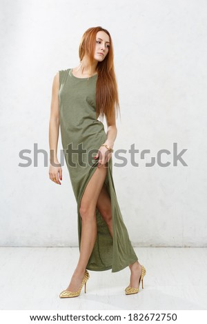 Skinny girl with long legs in green dress posing against a white textured wall - stock photo