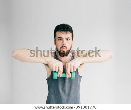 Skinny man training his bicep muscle.  - stock photo