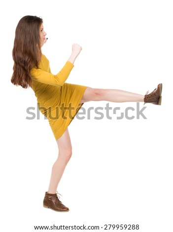 skinny woman funny fights waving his arms and legs. Isolated over white background. Girl engineer in the yellow dress standing right side and hit his left foot. - stock photo