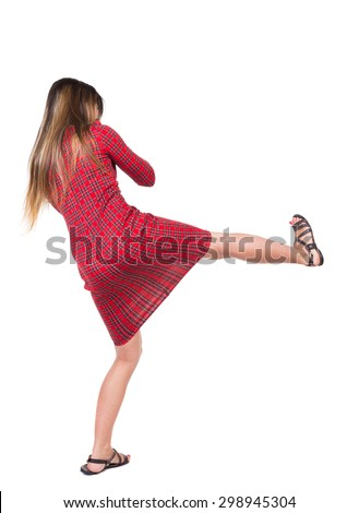 skinny woman funny fights waving his arms and legs. Isolated over white background. Long-haired girl in a red plaid dress hits right foot. - stock photo