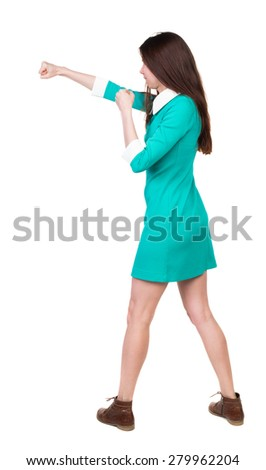 skinny woman funny fights waving his arms and legs. Isolated over white background. The girl in a dress beats foot in brown shoe. The girl in the green dress has a strict right hand. - stock photo