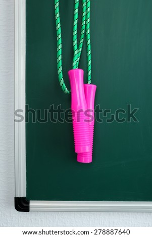 Skipping rope on green blackboard background - stock photo