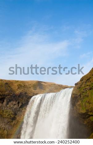 skogafoss cascade and a cloud over it - stock photo