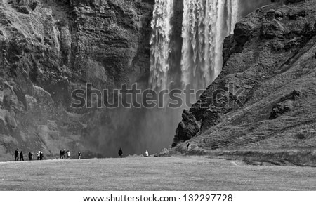 Skogafoss waterfall and rainbow in Iceland (black and white) - stock photo