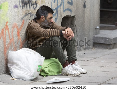 Skopje, Macedonia - May 14, 2015: A homeless beggar is begging on a busy street in the center of Skopje. Macedonia is still one of the poorest countries in the Balkans. - stock photo