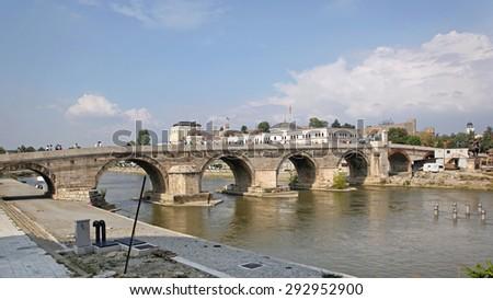 SKOPJE, MACEDONIA - SEPTEMBER 17: The Stone Bridge in Skopje on SEPTEMBER 17, 2012. Old Bridge Over Vardar River Cityscape in Skopje, Macedonia. - stock photo