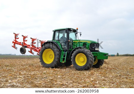 Skrzelew - October 09: Tractor-driver presenting a new model John Deere tractor (7530 series) with a reversible ploughs, during the XIII Days of Corn on October 09, 2011 in Skrzelew, Poland. - stock photo