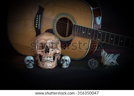 Skull and Acoustic guitar on dark background (Still life style)