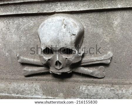 skull and bones at an ancient gravestone - stock photo