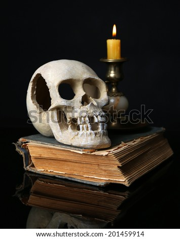Skull and candle on old book isolated on black - stock photo