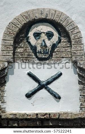 Skull and cross bones on a wall in Elmina castle in Ghana - stock photo