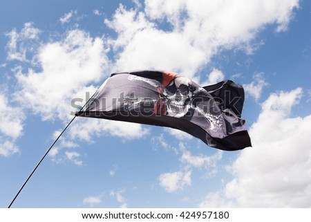 Skull and cross bones pirate flag waving in the wind. - stock photo